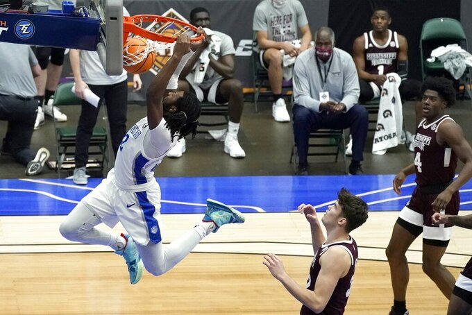 Saint Louis forward Terrence Hargrove Jr. (22) dunks the ball after getting past Mississippi State forward Quinten Post (32) as Cameron Matthews (4) looks on in the first half of an NCAA college basketball game in the first round of the NIT, Saturday, March 20, 2021, in Frisco, Texas. (AP Photo/Tony Gutierrez)