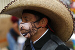 A man wearing a face mask walks amidst outdoor stalls at Mercado Sonora, which reopened ten days ago with measures to reduce congestion and limit the spread of the coronavirus, in Mexico City, Thursday, June 25, 2020. (AP Photo/Rebecca Blackwell)