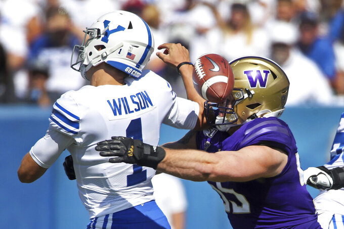 BYU quarterback Zach Wilson (1) fumbles the ball as he is hit by Washington linebacker Ryan Bowman (55) in the first half during an NCAA college football game, Saturday, Sept. 21, 2019, in Provo, Utah. (AP Photo/George Frey)