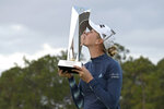 Jessica Korda kisses the championship trophy on the 18th green after winning in a one-hole playoff against Danielle Kang during the final round of the Tournament of Champions LPGA golf tournament, Sunday, Jan. 24, 2021, in Lake Buena Vista, Fla. (AP Photo/Phelan M. Ebenhack)