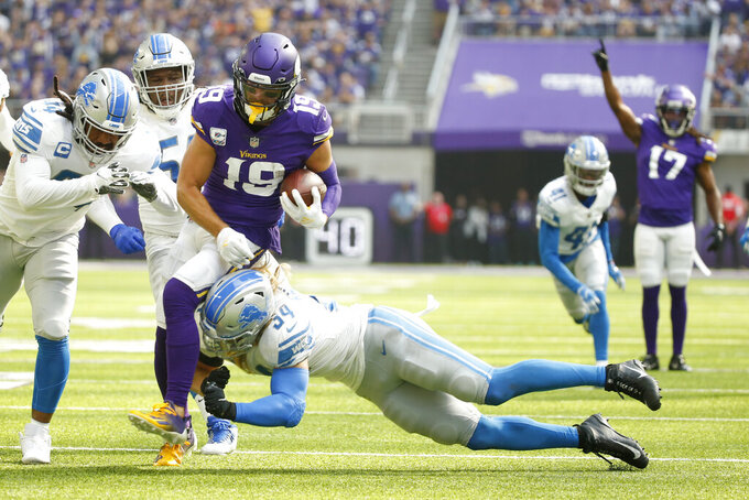 Minnesota Vikings wide receiver Adam Thielen (19) tries to break a tackle by Detroit Lions nose tackle Alim McNeill (54) after catching a pass during the first half of an NFL football game, Sunday, Oct. 10, 2021, in Minneapolis. (AP Photo/Bruce Kluckhohn)