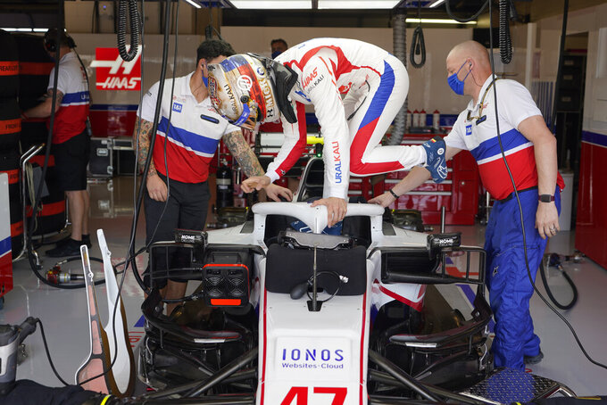Haas driver Mick Schumacher, of Germany, climbs into his car during a practice session for the F1 US Grand Prix auto race at Circuit of the Americas, Friday, Oct. 22, 2021, in Austin, Texas. (AP Photo/Darron Cummings)
