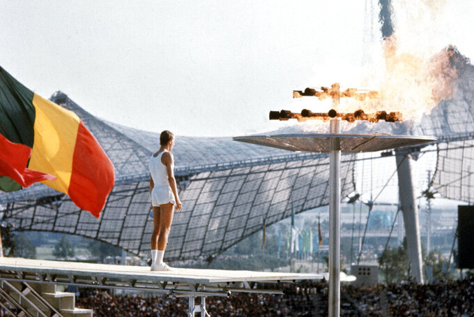FILE - In this Aug. 26, 1972, file photo, West German middle distance runner, junior athlete Guenther Zahn (18), stands near the Olympic flame he lit above the Olympic Stadium during the opening ceremony of the Summer Olympic Games in Munich, Germany. (AP Photo/File)