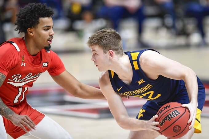 West Virginia's Sean McNeil (22) controls the ball against Texas Tech's Kyler Edwards (11) during the first half of an NCAA college basketball game in Lubbock, Texas, Tuesday, Feb. 9, 2021. (AP Photo/Justin Rex)