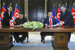 FILE - In this June 12, 2018, file photo, North Korea leader Kim Jong Un, center left, and U.S. President Donald Trump, center right, prepare to sign a document at the Capella resort on Sentosa Island in Singapore. At the last minute, Kim's sister, Kim Yo-jong, far left, provided a pen of her own for his use. After the name of Kim Yo Jong was found to be missing from North Korea's newly released lineup for its powerful Politburo, speculation has been rife about the woman widely viewed as the North's No.2. (AP Photo/Evan Vucci, File)