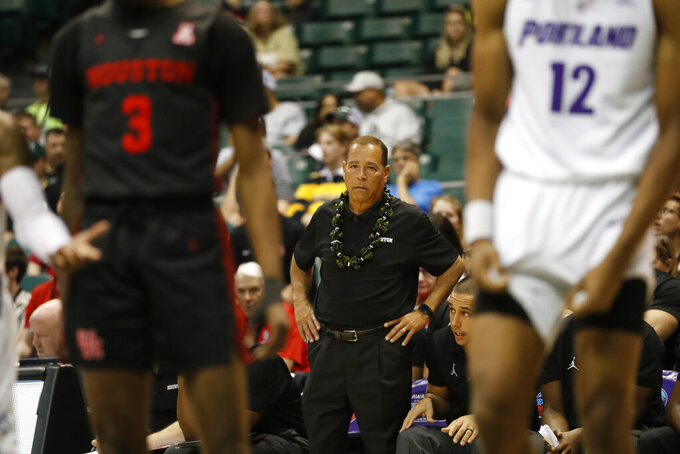 Houston head coach Kelvin Sampson, center, watches his team take on Portland during the second half of an NCAA college basketball game Sunday, Dec. 22, 2019, in Honolulu. (AP Photo/Marco Garcia)