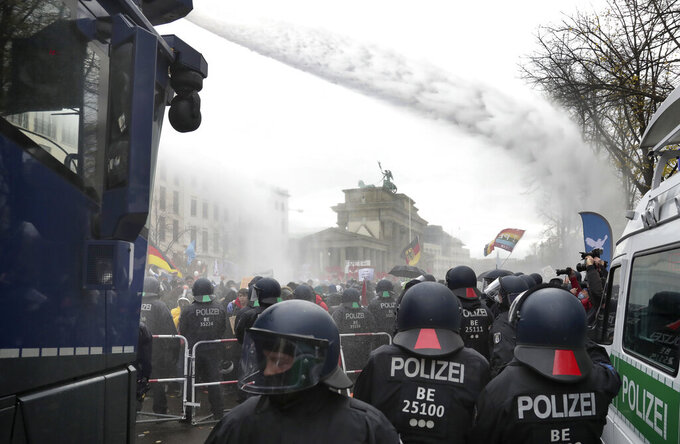 File - In this Wednesday, Nov. 18, 2020 file photo, police uses water canons to clear a blocked a road between the Brandenburg Gate and the Reichstag building, home of the German federal parliament, as people attend a protest rally in Berlin, Germany, against the coronavirus restrictions in Germany. Authorities in Germany say the number of far-right extremists in the country increased last year as neo-Nazis sought to join protests against pandemic-related restrictions. German Interior Minister Horst Seehofer said authorities counted 33,300 far-right extremists in 2020, an increase of almost 4% from the previous year. (AP Photo/Michael Sohn, file)