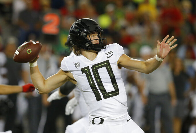 FILE - In this Oct. 27, 2018, file photo, Oregon quarterback Justin Herbert (10) throws during an NCAA college football game against Arizona, in Tucson, Ariz. As a soon-to-be senior, Oregon quarterback Justin Herbert knows this about spring football: It's a process and it's rarely smooth. A Eugene native, Herbert will be joined this coming season by his younger brother Patrick a tight end out of Thousand Oaks, California, who was among 10 early enrollees who are taking part in spring practice with the Ducks.(AP Photo/Rick Scuteri, File)