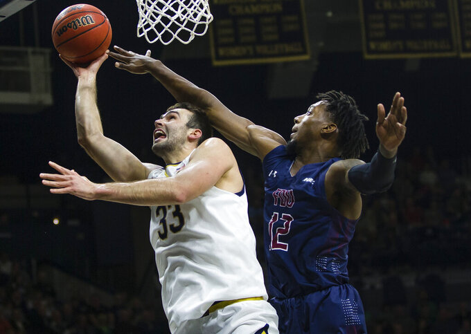 Notre Dame's John Mooney (33) shoots defended by Fairleigh Dickinson's Kaleb Bishop (12)  during an NCAA college basketball game  Tuesday, Nov. 26, 2019, in South Bend, Ind. (Michael Caterina/South Bend Tribune via AP)