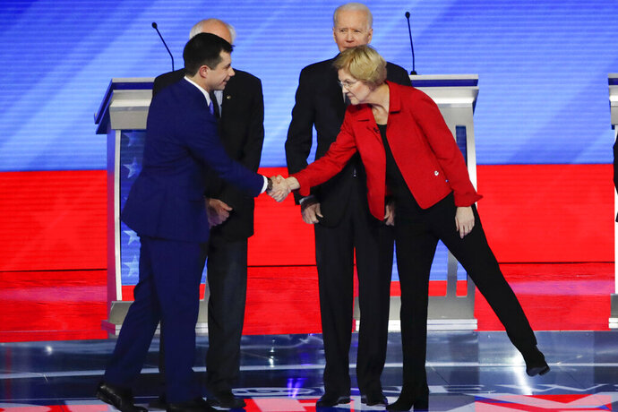 Democratic presidential candidates former South Bend Mayor Pete Buttigieg, left, shakes hands with Sen. Elizabeth Warren, D-Mass., right, as Sen. Bernie Sanders, I-Vt., back left, and former Vice President Joe Biden, back right, stand on stage Friday, Feb. 7, 2020, before the start of a Democratic presidential primary debate hosted by ABC News, Apple News, and WMUR-TV at Saint Anselm College in Manchester, N.H. (AP Photo/Elise Amendola)