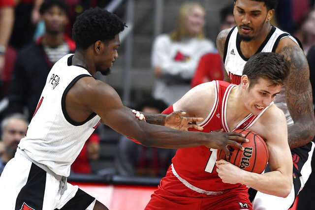 Louisville guard Darius Perry (2) tries to strip the ball away from Miami (Ohio) guard Milos Jovic (15) during the second half of an NCAA college basketball game in Louisville, Ky., Wednesday, Dec. 18, 2019. Louisville won 70-46. (AP Photo/Timothy D. Easley)