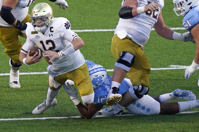 North Carolina linebacker Tomon Fox sacks Notre Dame quarterback Ian Book (12) during the first half of an NCAA college football game in Chapel Hill, N.C., Friday, Nov. 27, 2020. (AP Photo/Gerry Broome)