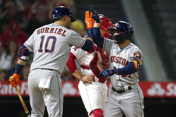 Houston Astros' Jose Altuve, right, celebrates his two-run home run with Yuli Gurriel (10) during the fifth inning of a baseball game against the Los Angeles Angels Tuesday, Sept. 21, 2021, in Anaheim, Calif. (AP Photo/Marcio Jose Sanchez)
