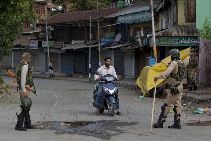 Indian paramilitary soldiers turn back a Kashmiri motorist near a temporary check point during lockdown in Srinagar, Indian controlled Kashmir, Sunday, Aug. 18, 2019. (AP Photo/ Dar Yasin)