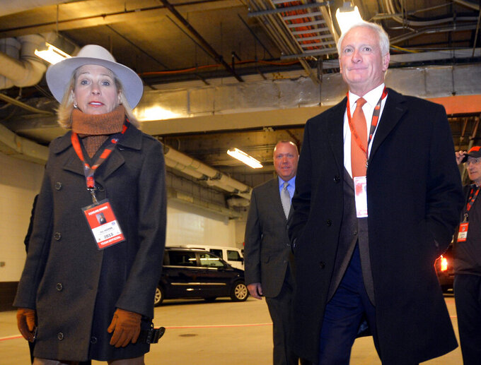 FILE - In this Nov. 30, 2015, file photo, Cleveland Browns owner Jimmy Haslam, right, and his wife Dee Haslam walk to the playing field before an NFL football game against the Baltimore Ravens in Cleveland. Browns owners Dee and Jimmy Haslam will stand in support of quarterback Baker Mayfield and any other Cleveland players who kneel during the national anthem this season. (AP Photo/David Richard, File)