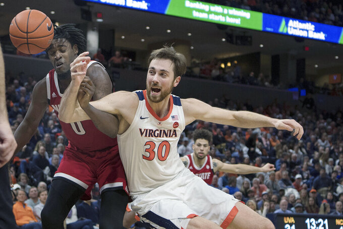 Virginia center Jay Huff (30) and North Carolina State forward D.J.Funderburk (0) battle for rebound during the second half of an NCAA college basketball game in Charlottesville, Va., Monday, Jan. 20, 2020. (AP Photo/Lee Luther Jr.)