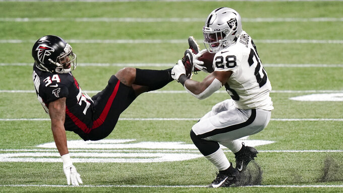 Las Vegas Raiders running back Josh Jacobs (28) hits Atlanta Falcons defensive back Darqueze Dennard (34) during the first half of an NFL football game, Sunday, Nov. 29, 2020, in Atlanta. (AP Photo/Brynn Anderson)