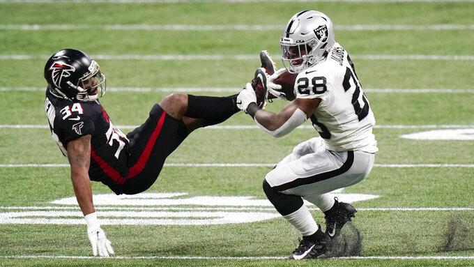 Las Vegas Raiders running back Josh Jacobs (28) hits Atlanta Falcons defensive back Darqueze Dennard (34) during the first half of an NFL football game, Sunday, Nov. 29, 2020, in Atlanta. (AP Photo/Brynn Anderson)