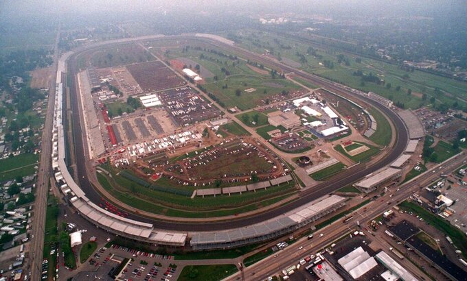 FILE - In this May 24, 1996, file photo, a cloud hangs over the Indianapolis Motor Speedway in this photo taken from the Goodyear blimp. Turn one is at the lower left. Indianapolis Motor Speedway and the IndyCar Series have been sold to Penske Entertainment Corp. in a stunning announcement that relinquishes control of the iconic speedway from the Hulman family after 74 years. (AP Photo/ John R. Fulton Jr., File )