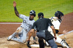 Chicago White Sox's Tim Anderson (7) scores as Pittsburgh Pirates catcher Jacob Stallings receives the late relay throw during the fifth inning of a baseball game in Pittsburgh, Tuesday, Sept. 8, 2020. Making the call is umpire Jeremie Rehak. (AP Photo/Gene J. Puskar)