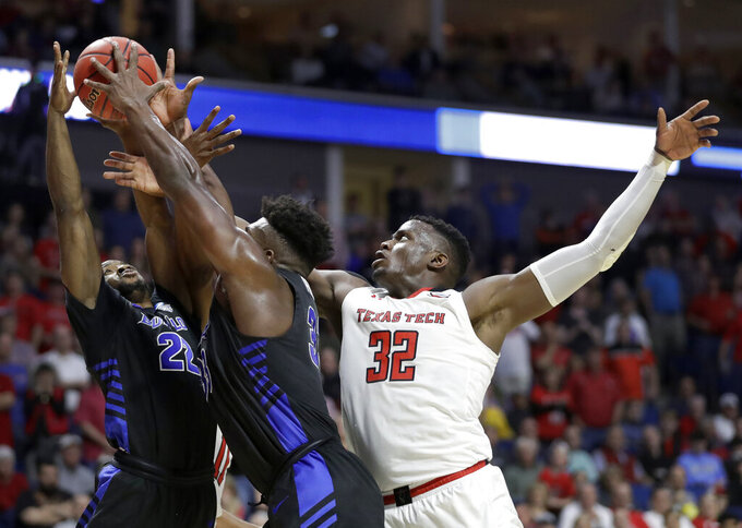 Texas Tech's Norense Odiase (32) reaches for a rebound along with Buffalo's Dontay Caruthers (22) and Nick Perkins during the first half of a second round men's college basketball game in the NCAA Tournament Sunday, March 24, 2019, in Tulsa, Okla. (AP Photo/Jeff Roberson)