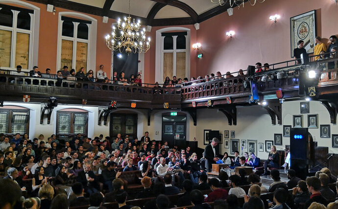 In this photo taken on Thursday, Nov. 21, 2019, audience members look on during a debate on the threat of artificial intelligence at the Cambridge Union, the world's oldest debating society, Cambridge, England. IBM's artificial intelligence debating robot faced off against itself at Cambridge University, in a demonstration of what the future might hold. Project Debater, a robot that has already debated humans, was for the first time pitted against itself, at least in the first round of arguments at the Cambridge Union, the world's oldest debating society. (AP Photo/James Brooks)