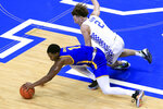 Morehead State's DeVon Cooper (1) tries to pull in the ball while pressured by Kentucky's Devin Askew (2) during the first half of an NCAA college basketball game in Lexington, Ky., Wednesday, Nov. 25, 2020. (AP Photo/James Crisp)