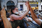 Protesters, left, clash with police officers preventing them from marching against the government's decision to withdraw from Istanbul Convention, in Istanbul, Thursday, July 1, 2021. Turkey formally withdrew Thursday from the landmark international treaty protecting women from violence, and signed in its own city of Istanbul, though President Recep Tayyip Erdogan insisted it won't be a step backwards for women. Women, LGBT groups and others have been protesting the decision, saying the convention's pillars of prevention, protection, criminal prosecution and policy coordination, as well as its identification of gender-based violence, are crucial to protecting women in Turkey. (AP Photo/Kemal Aslan)