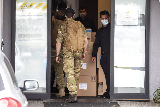 Military personnel enter the Sudima Hotel in Christchurch, New Zealand, Tuesday, Oct. 20, 2020. A number of fishing crew who flew into New Zealand on chartered planes have the coronavirus. The crew members have been in quarantine at the Christchurch hotel since they arrived, and tested positive during routine testing, officials said. The news could deal a blow to New Zealand's efforts to restart its fishing industry, which has struggled to find local workers to crew fishing vessels.  (AP Photo/Mark Baker)