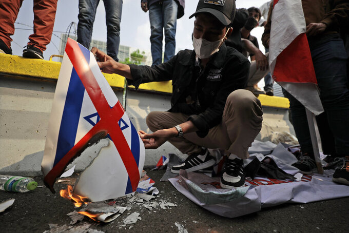 A Muslim student burns a poster of a defaced Israeli flag during a rally against Israel's attacks on Gaza, outside the U.S. Embassy in Jakarta, Indonesia, Friday, May 21, 2021. (AP Photo/Dita Alangkara)