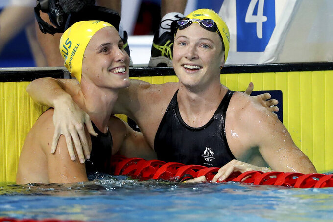 FILE - In this April 6, 2018, file photo, Australia's Cate Campbell, right, embraces her sister Bronte Campbell after their women's 50m freestyle semifinal at the Aquatic Centre during the 2018 Commonwealth Games on the Gold Coast, Australia. Even before the coronavirus pandemic, the Australian swimming siblings have had their share of health concerns. (AP Photo/Rick Rycroft, File)