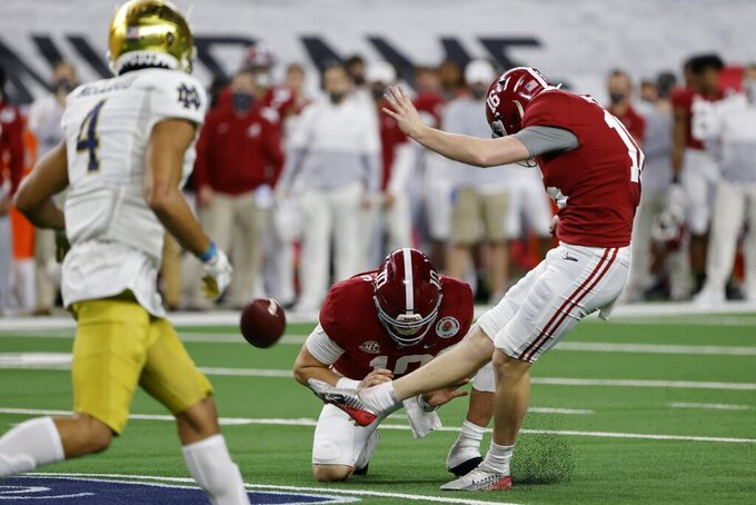 Notre Dame cornerback Nick McCloud (4) rushes as Alabama place kicker Will Reichard (16) kicks a field goal in the second half of the Rose Bowl NCAA college football game in Arlington, Texas, Friday, Jan. 1, 2021. Alabama's Mac Jones holds on the play. (AP Photo/Michael Ainsworth)
