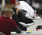 DeKalb Voter Registration and Elections workers begin scanning ballots to electronically recount votes by the state-mandated timeline, Tuesday, Nov 24, 2020, in Stonecrest, Ga. (Curtis Compton/Atlanta Journal-Constitution via AP)