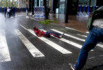 A person lay on a crosswalk after being knocked to the street by wind in lower Manhattan Tuesday, Aug. 4, 2020, as Tropical Storm Isaias produced strong winds as the storm moved past, at times causing damage. (AP Photo/Craig Ruttle)