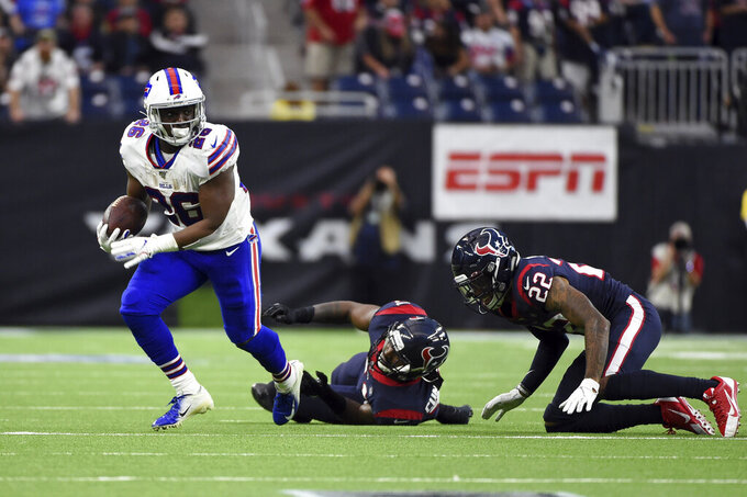 Buffalo Bills running back Devin Singletary (26) breaks away from Houston Texans inside linebacker Zach Cunningham, center, and Gareon Conley (22) during the first half of an NFL wild-card playoff football game Saturday, Jan. 4, 2020, in Houston. (AP Photo/Eric Christian Smith)