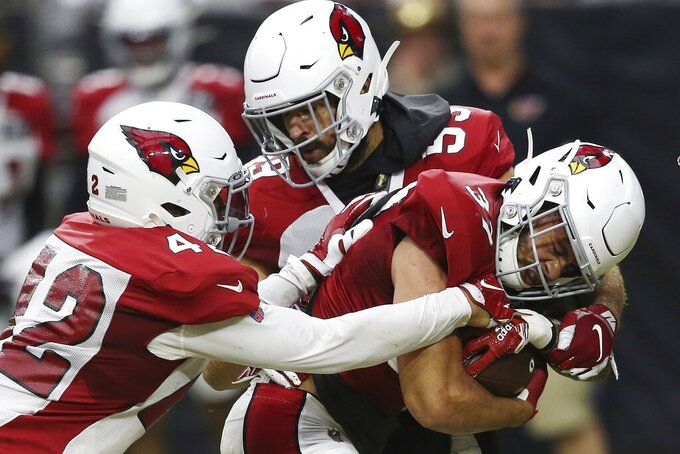 Arizona Cardinals running back D.J. Foster, right, gets tackled by defensive back Jonathan Owens (42) and linebacker Joe Walker, top, during NFL football training camp Wednesday, July 31, 2019, in Glendale, Ariz. (AP Photo/Ross D. Franklin)