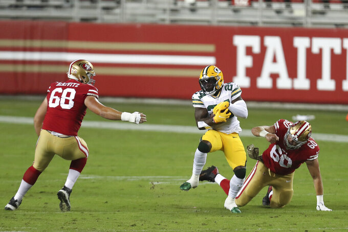 Green Bay Packers safety Raven Greene (24) returns an interception between San Francisco 49ers offensive tackle Colton McKivitz (68) and offensive guard Daniel Brunskill (60) during the first half of an NFL football game in Santa Clara, Calif., Thursday, Nov. 5, 2020. (AP Photo/Jed Jacobsohn)