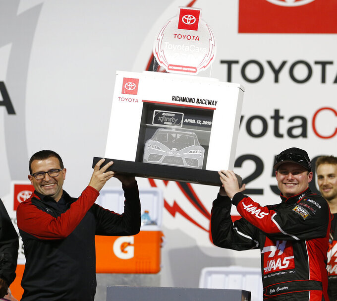 Cole Custer, right, holds the trophy along with track president Dennis Bickmeier, as he celebrates winning the NASCAR Xfinity Series auto race at Richmond Raceway in Richmond, Va., Friday, April 12, 2019. (AP Photo/Steve Helber)