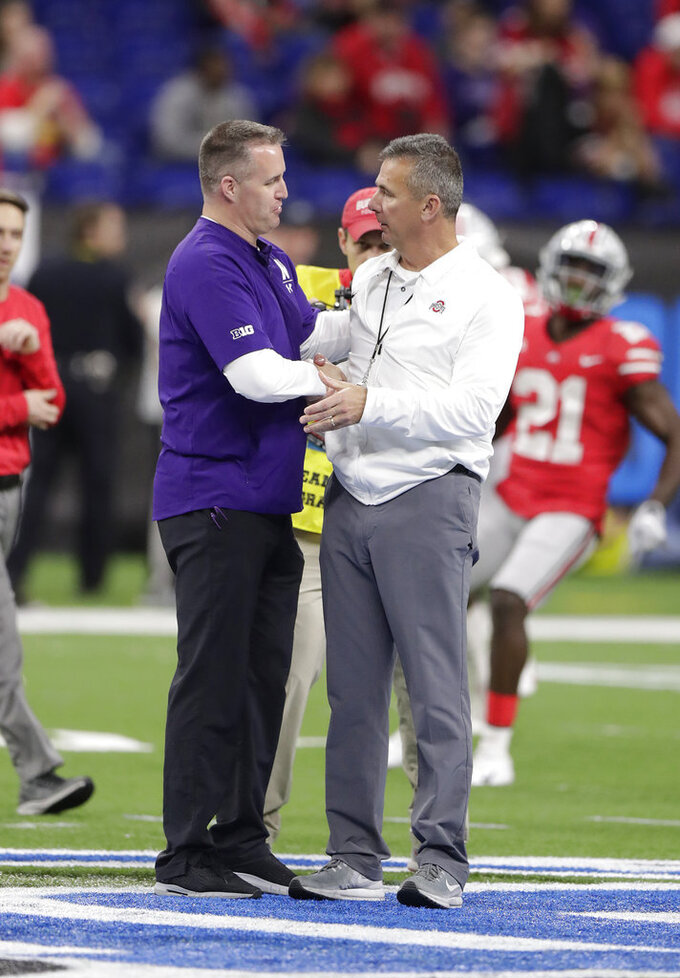 Northwestern coach Pat Fitzgerald, left, shakes hands with Ohio State coach Urban Meyer before the Big Ten championship NCAA college football game Saturday, Dec. 1, 2018, in Indianapolis. (AP Photo/Michael Conroy)