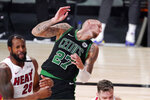 Boston Celtics' Daniel Theis (27) recoils from contact with Miami Heat's Andre Iguodala (28) during the second half of an NBA conference final playoff basketball game Friday, Sept. 25, 2020, in Lake Buena Vista, Fla. (AP Photo/Mark J. Terrill)