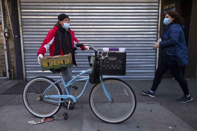 A man balances boxes of food that he picked up from Masbia Soup Kitchen, Thursday, March 26, 2020 during the coronavirus pandemic in the Brooklyn borough of New York. The new coronavirus causes mild or moderate symptoms for most people, but for some, especially older adults and people with existing health problems, it can cause more severe illness or death. (AP Photo/Mark Lennihan)