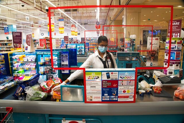 In this April 19, 2020 photo, cashier Valancy Fernandes of India, wearing a surgical mask and gloves to help prevent the spread of coronavirus, works at a Carrefour supermarket in Dubai, United Arab Emirates. Frontline workers across Arab Gulf countries are uniquely almost entirely foreigners. They risk exposure to the novel coronavirus, ensuring patients are cared for, streets are sanitized, packages are delivered and grocery stores are stocked. The global pandemic has drawn attention to just how vital foreigners are to the Arab Gulf countries where they work. (AP Photo/Jon Gambrell)