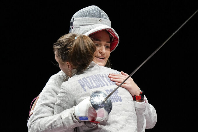 Sofia Pozdniakova, left, Hughs Sofya Velikaya of the Russian Olympic Committee as she celebrates after winning the gold at the women's individual Sabre final competition at the 2020 Summer Olympics, Monday, July 26, 2021, in Chiba, Japan. (AP Photo/Andrew Medichini)