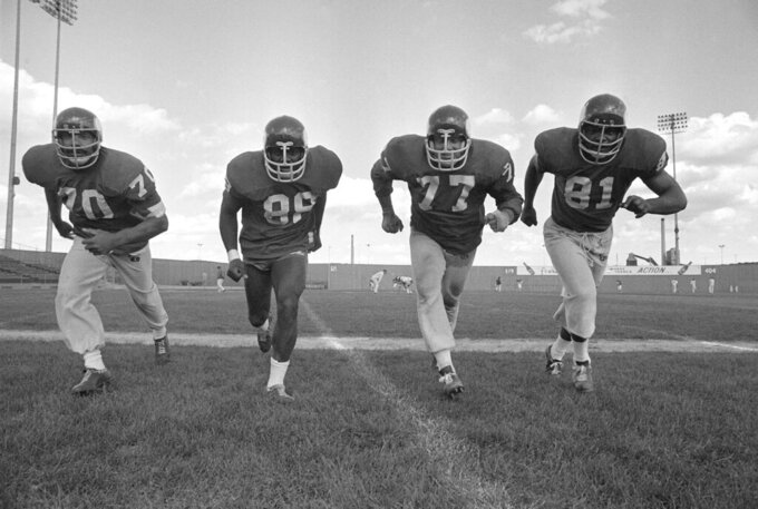 FIEL- In this Sept. 16, 1971 , file photo, the powerful defensive front four of the Minnesota Vikings , from left, Jim Marshall, Alan Page, Gary Larson, Carl Eller pose during NFL football practiced in Minneapolis. Helmets have evolved from the original hard leather of the NFL's infancy to hard polycarbonate single-piece shells with various amounts of padding and air bladders that served as the primary form of head protection into the beginning of this century. (AP Photo/File)
