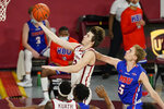 Oklahoma guard Austin Reaves (12) goes to the basket in front of Houston Baptist guard Hunter Janacek (5) in the first half of an NCAA college basketball game Saturday, Dec. 19, 2020, in Norman, Okla. (AP Photo/Sue Ogrocki)