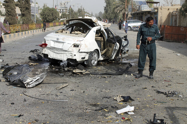 An Afghan policeman investigates a damaged car following a sticky bomb attack in Helmand province, southern Afghanistan, Thursday, Nov. 12, 2020. A bomb attached to the vehicle of a radio journalist in southern Afghanistan exploded early Thursday, killing him, a provincial official said. (AP Photo/Abdul Khaliq)