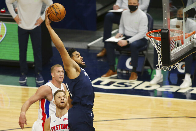 Minnesota Timberwolves forward Karl-Anthony Towns dunks in front Detroit Pistons forward Blake Griffin and center Mason Plumlee, rear, during the first quarter of an NBA basketball game Wednesday, Dec. 23, 2020, in Minneapolis. (AP Photo/Andy Clayton-King)
