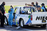 Driver Natalie Decker, second from left, waits for the start of a NASCAR Truck Series auto race at Kansas Speedway in Kansas City, Kan., Friday, July 24, 2020. (AP Photo/Charlie Riedel)