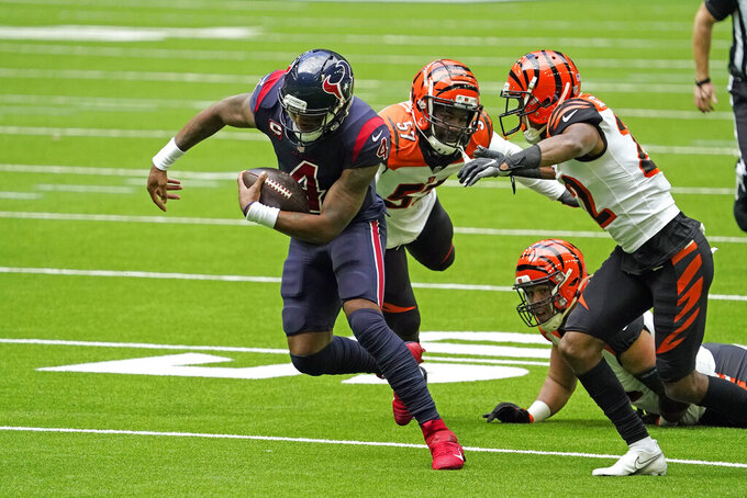 Houston Texans' Deshaun Watson (4) scrambles away from Cincinnati Bengals' Germaine Pratt (57) and William Jackson III (22) during the first half of an NFL football game Sunday, Dec. 27, 2020, in Houston. (AP Photo/Sam Craft)