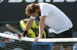 Latvia's Ernests Gulbis rests on the net, defeating Canada's Felix Auger-Aliassime in their first round singles match at the Australian Open tennis championship in Melbourne, Australia, Tuesday, Jan. 21, 2020. (AP Photo/Dita Alangkara)